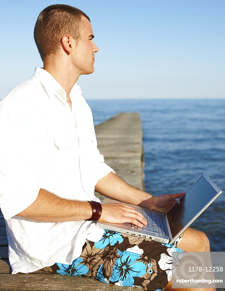 Young man using laptop on dock