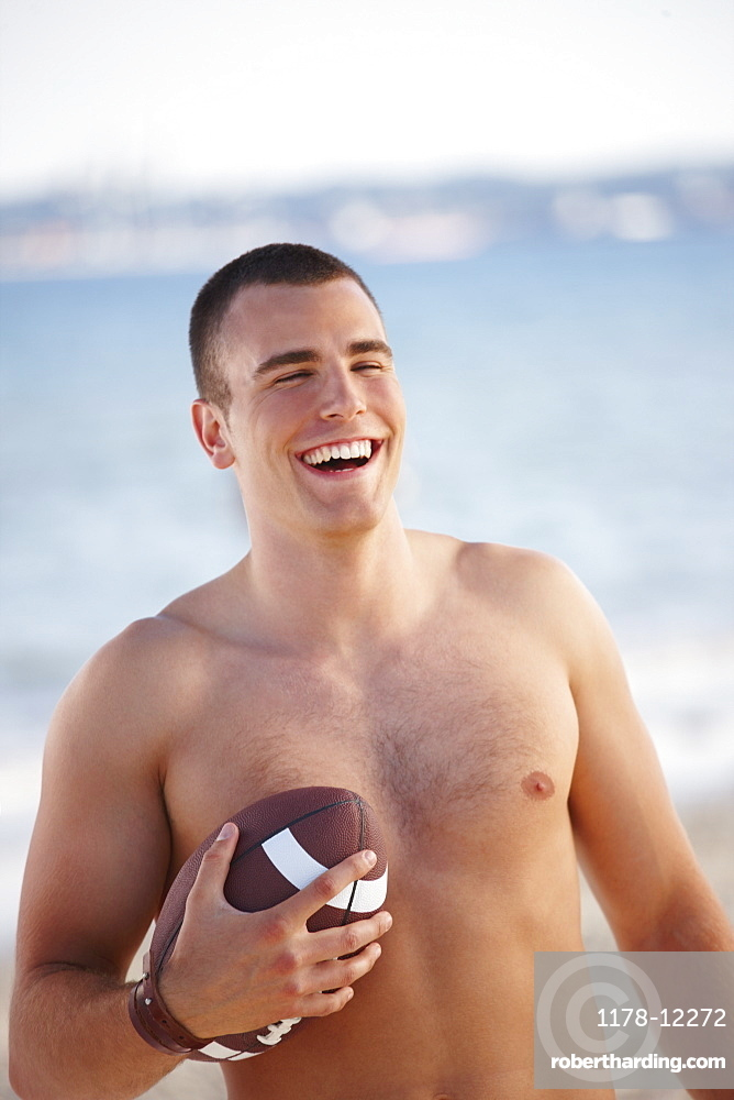 Young man holding football on beach