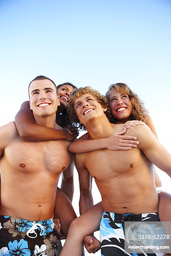 Young men carrying girlfriends on backs