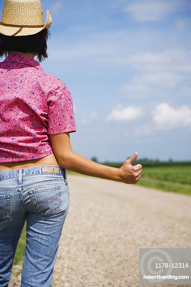 Teenage girl hitchhiking on rural road