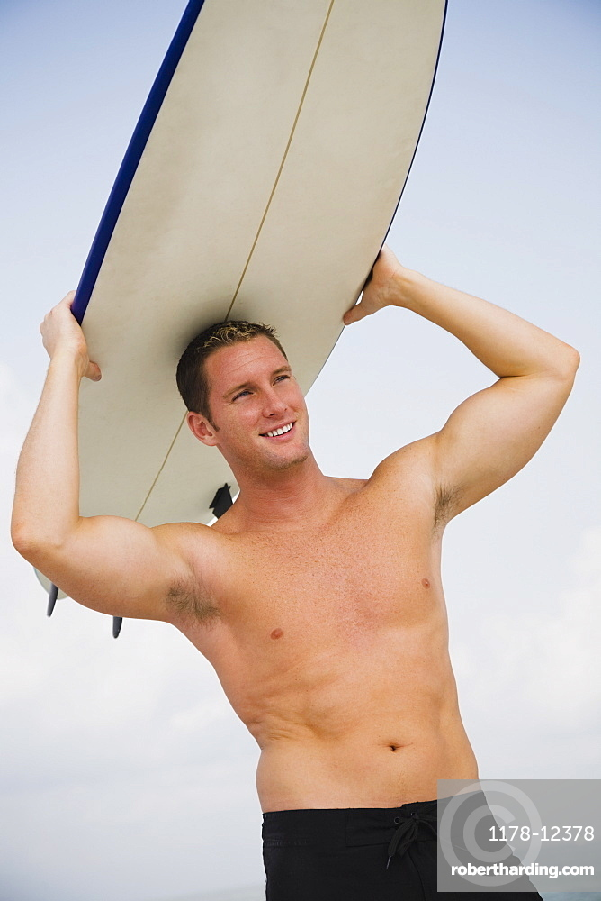 Bare-chested man holding surfboard
