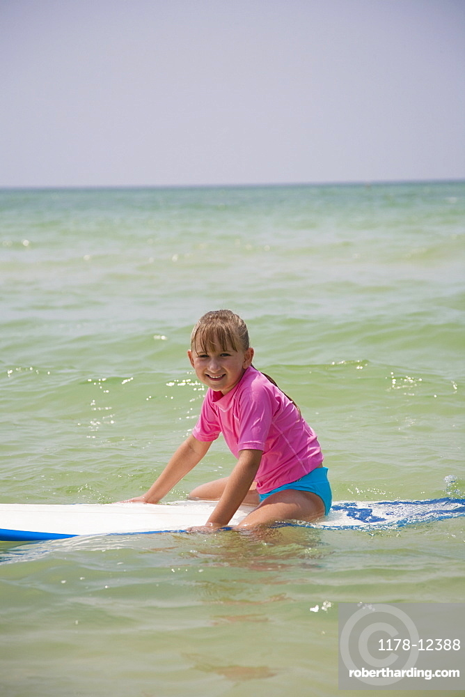 Young girl sitting on boogie board, Florida, United States