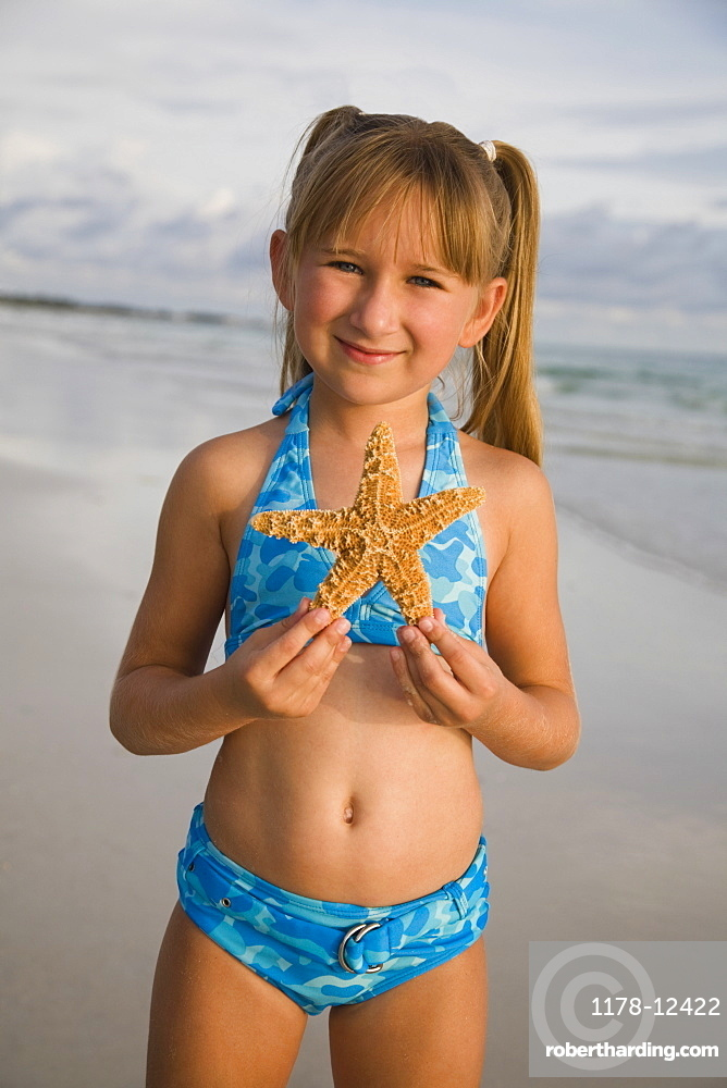 Girl holding up starfish, Florida, United States