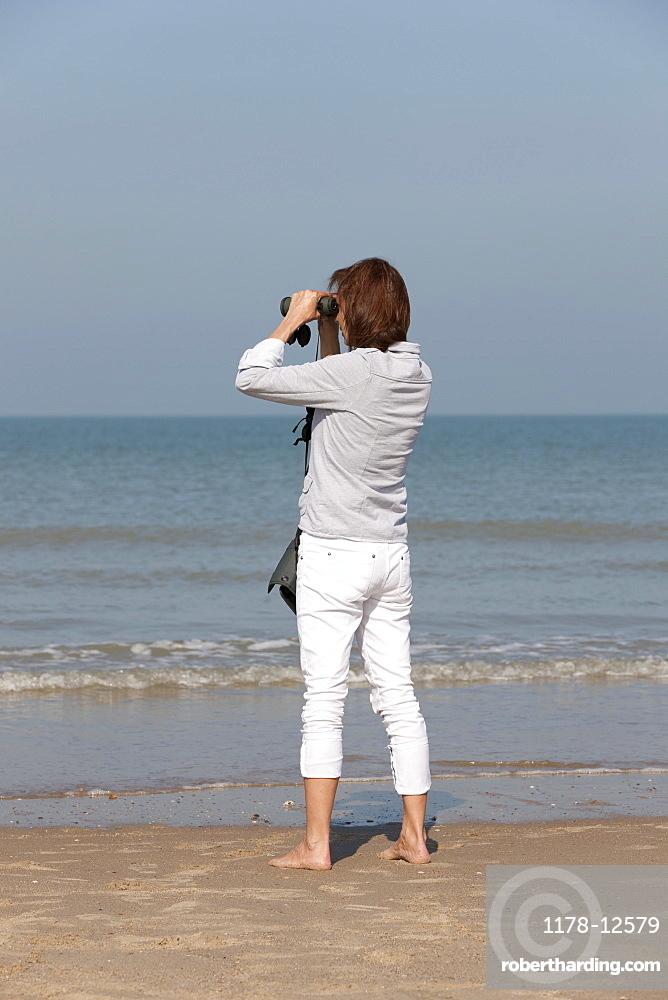 Woman on beach looking through binoculars