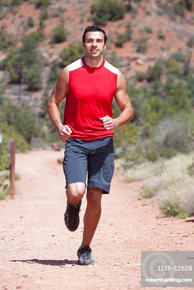 USA, Arizona, Sedona, Young man running in desert