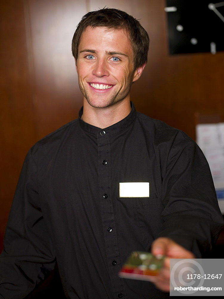 Young male receptionist giving card
