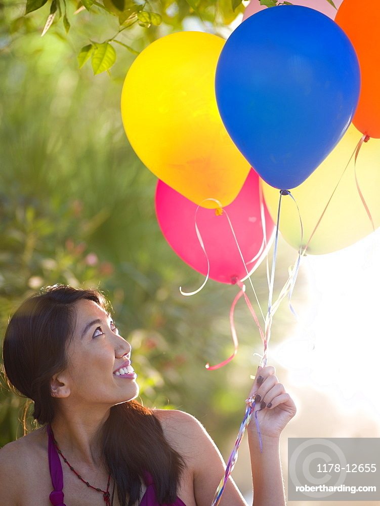 Mid adult woman holding balloons