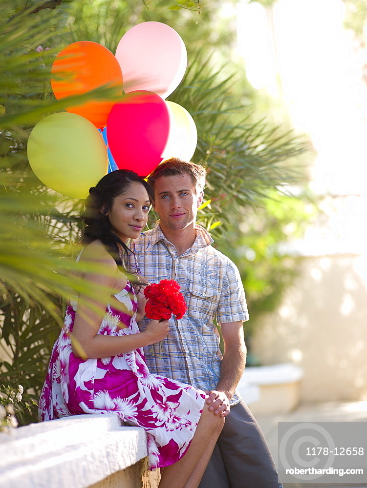 Young couple with balloons and roses