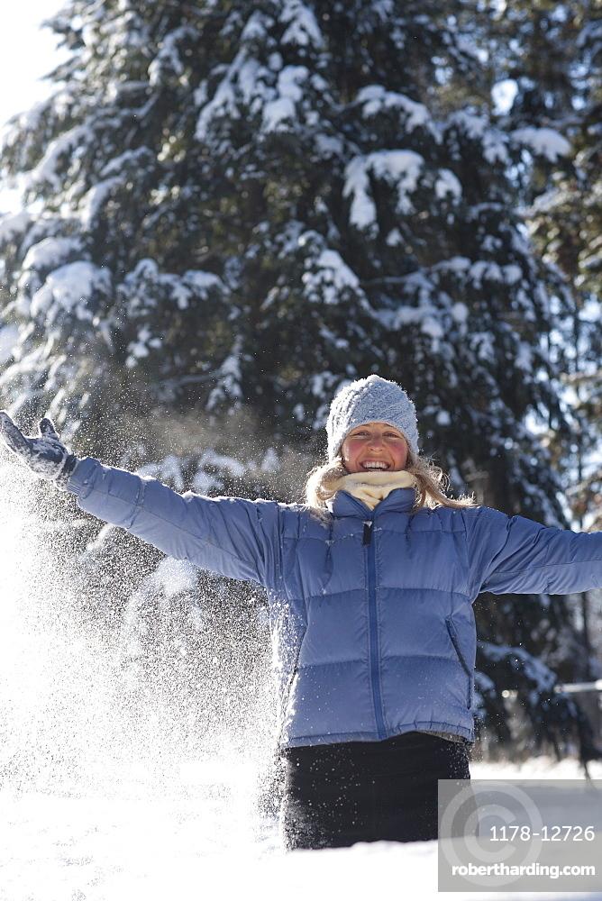USA, Montana, Whitefish, Woman playing in snow