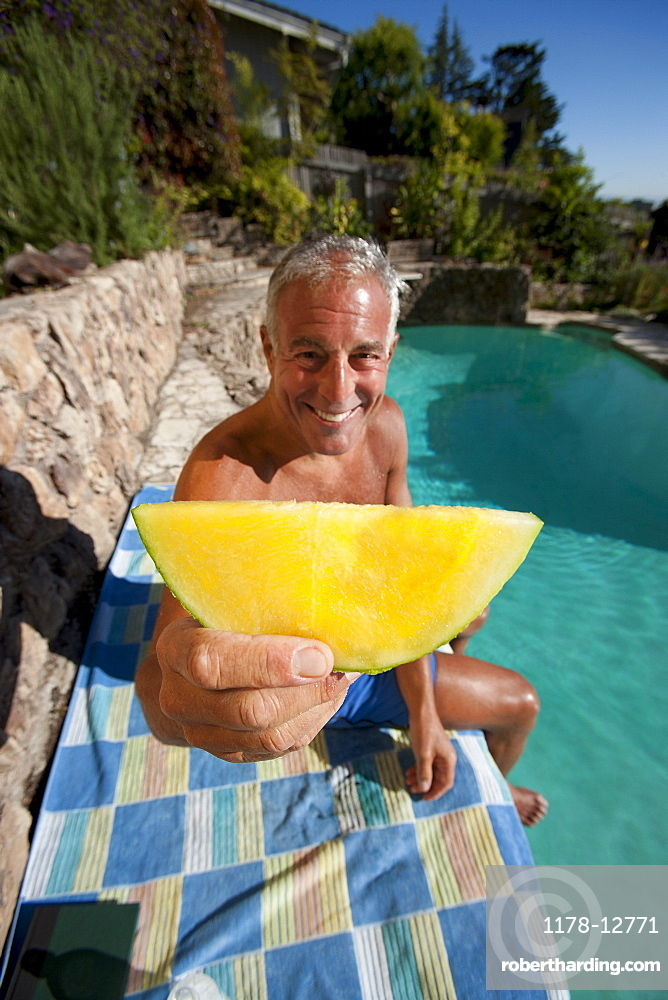 USA, California, Oakland, Senior man relaxing at swimming pool