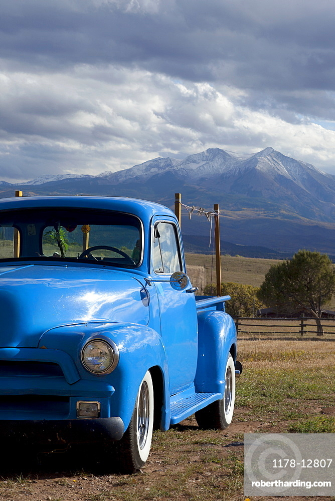 USA, Colorado, Carbondale, Blue vintage car, mount Sopris in background