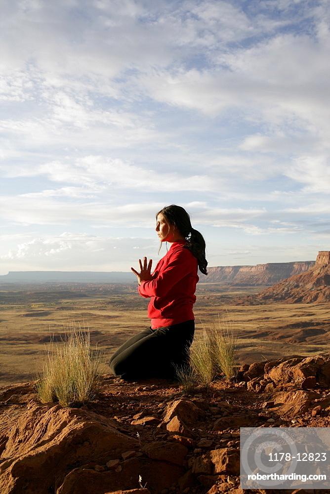 USA, Utah, Canyonlands National Park, woman meditating on rock