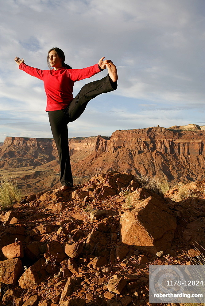 USA, Utah, Canyonlands National Park, woman stretching on rock