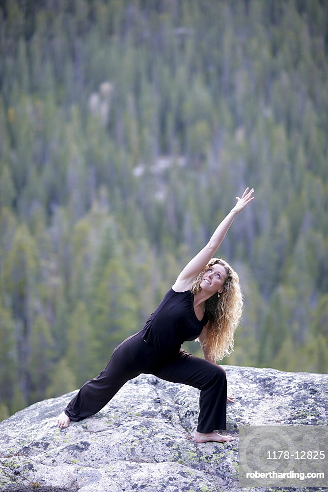 USA, Colorado, Aspen, woman stretching on rock