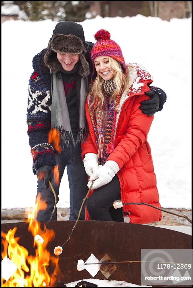 USA, Utah, Salt Lake City, couple cooking barbecue in winter