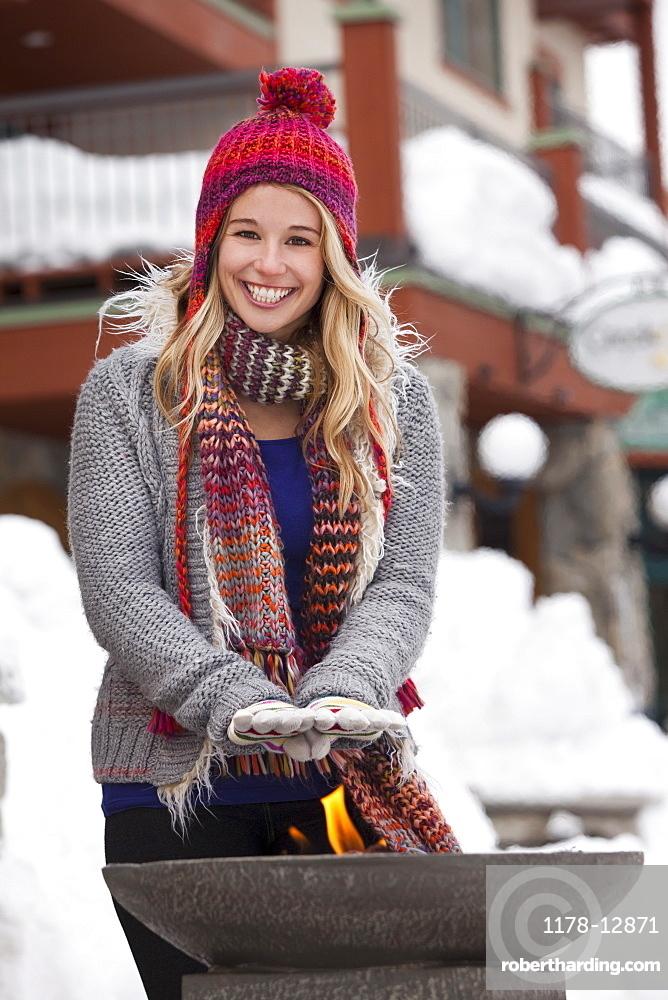USA, Utah, Salt Lake City, young woman warming hands over burner in ski resort