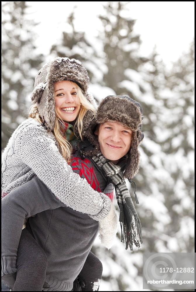 USA, Utah, Salt Lake City, man giving young woman piggy back ride in snow