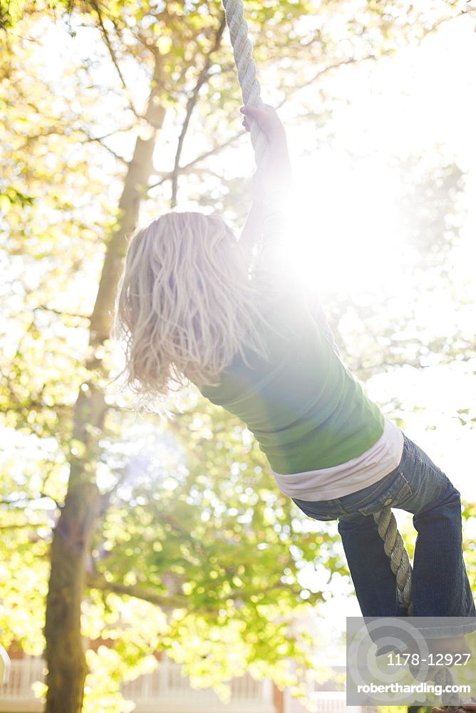 USA, Utah, rear view of girl (8-9) hanging on rope