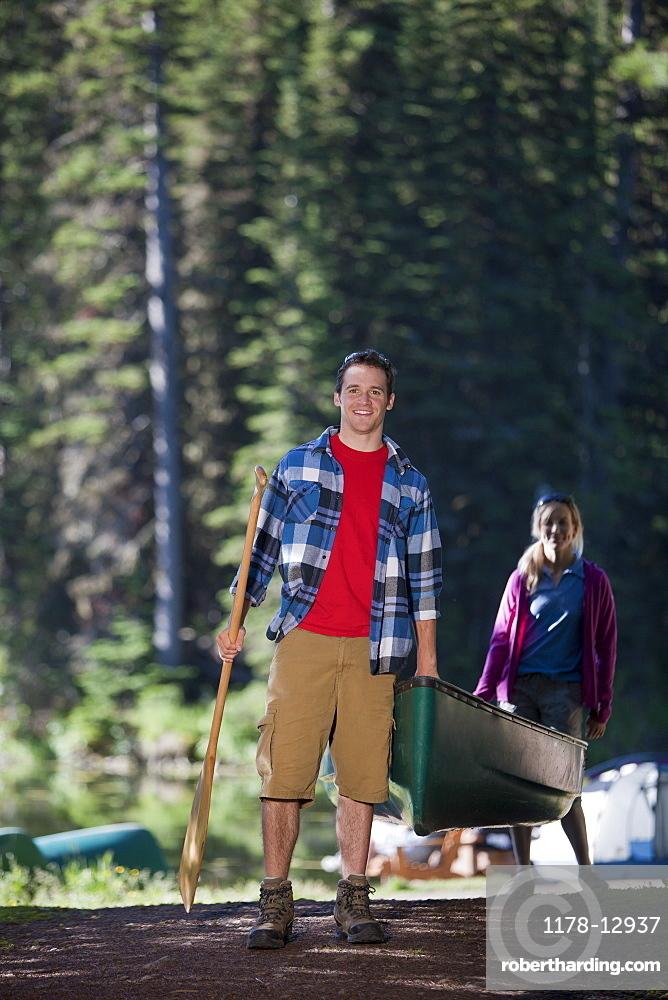 Canada, British Columbia, Fernie, Couple carrying canoe