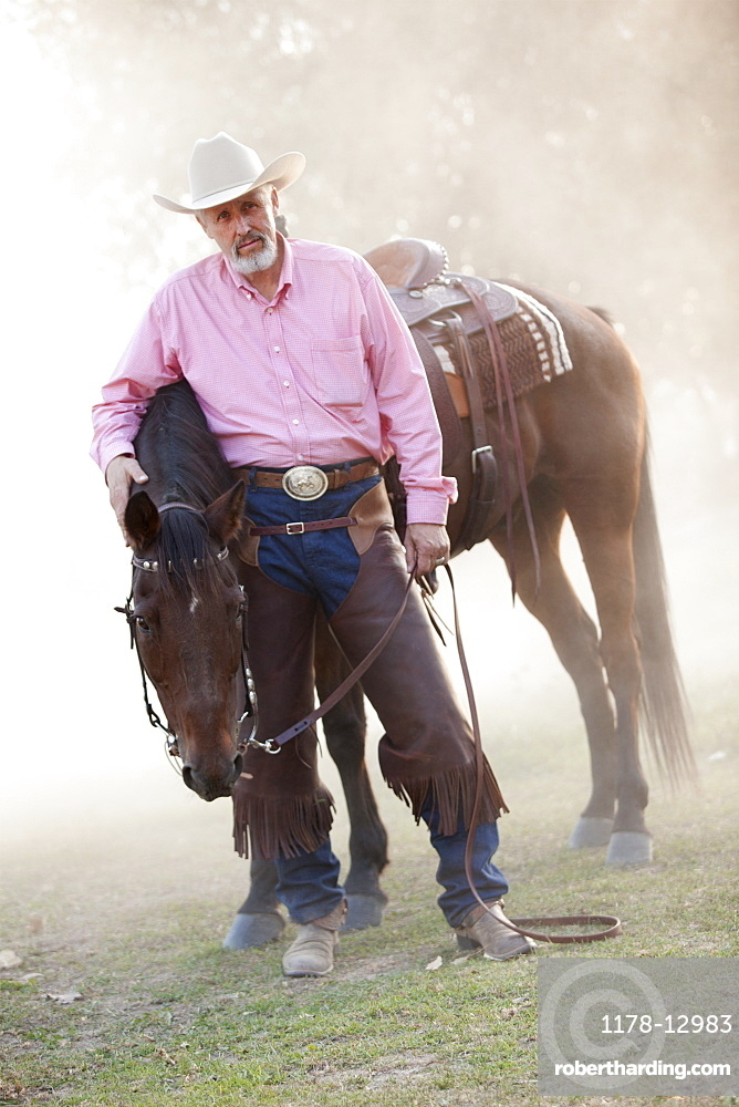 Portrait of senior man with horse in ranch
