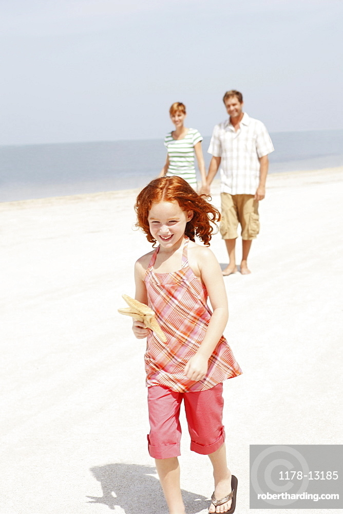 Couple and daughter walking on beach