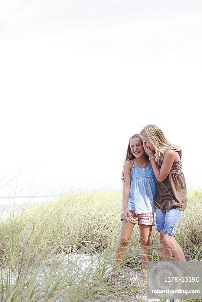 Girls whispering in beach grass