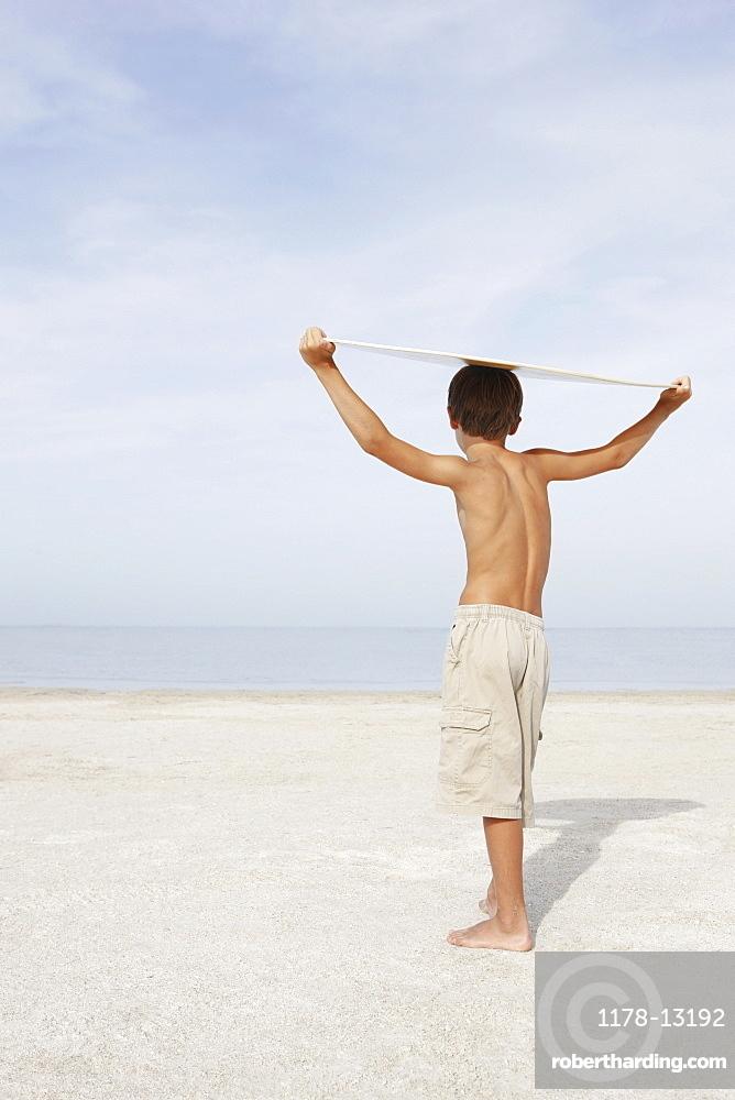 Boy standing on beach holding bodyboard overhead