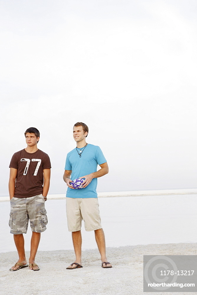 Young men standing on beach with football