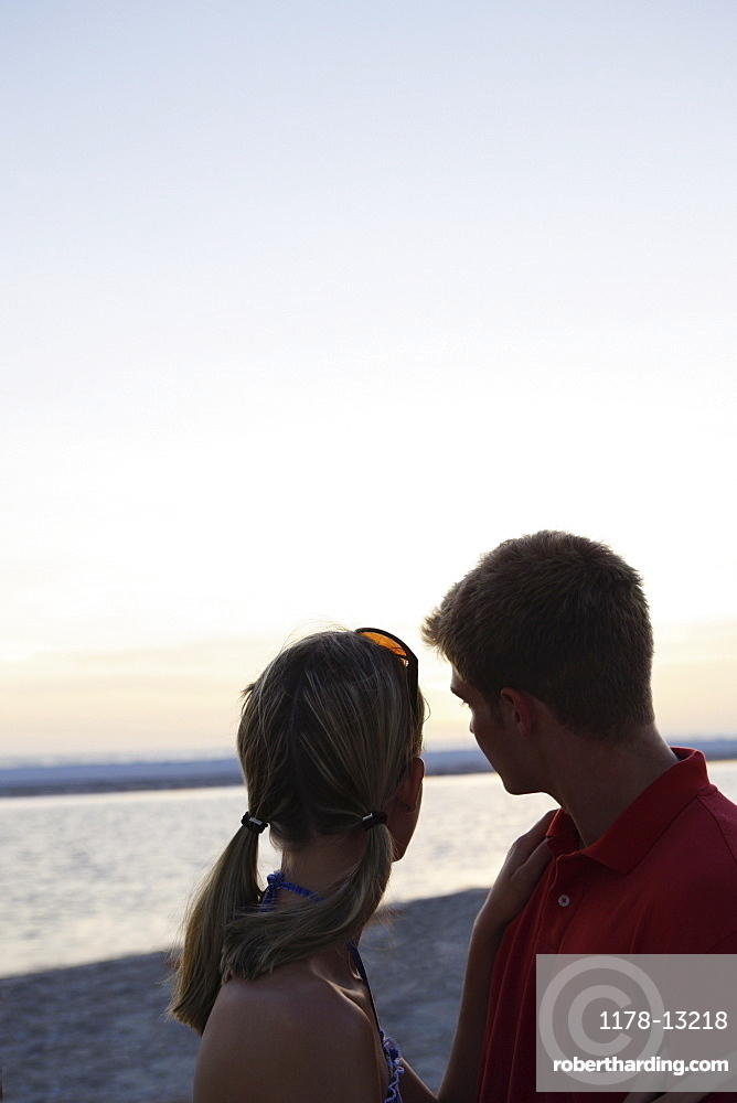 Young couple hugging on beach at sunset