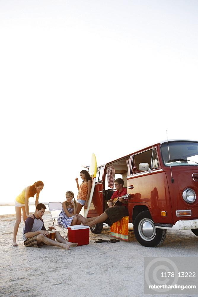 Friends socializing around van on beach