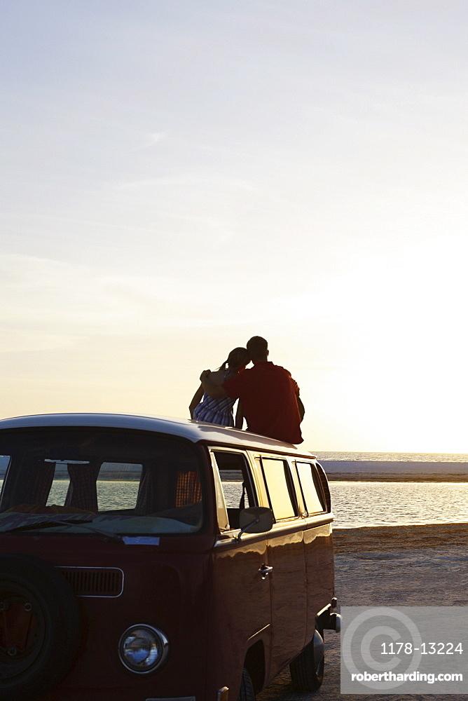 Couple watching ocean sunset from top of van