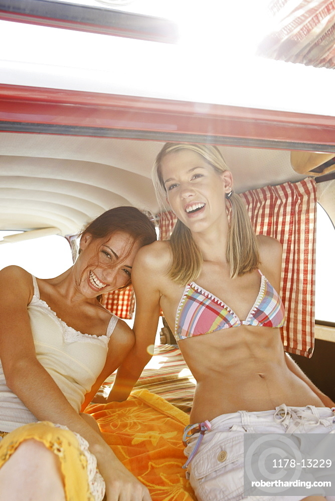 Young women relaxing in van on beach