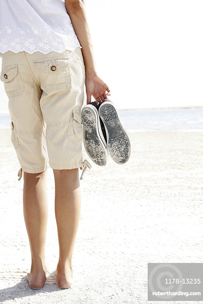 Young woman walking barefoot on beach