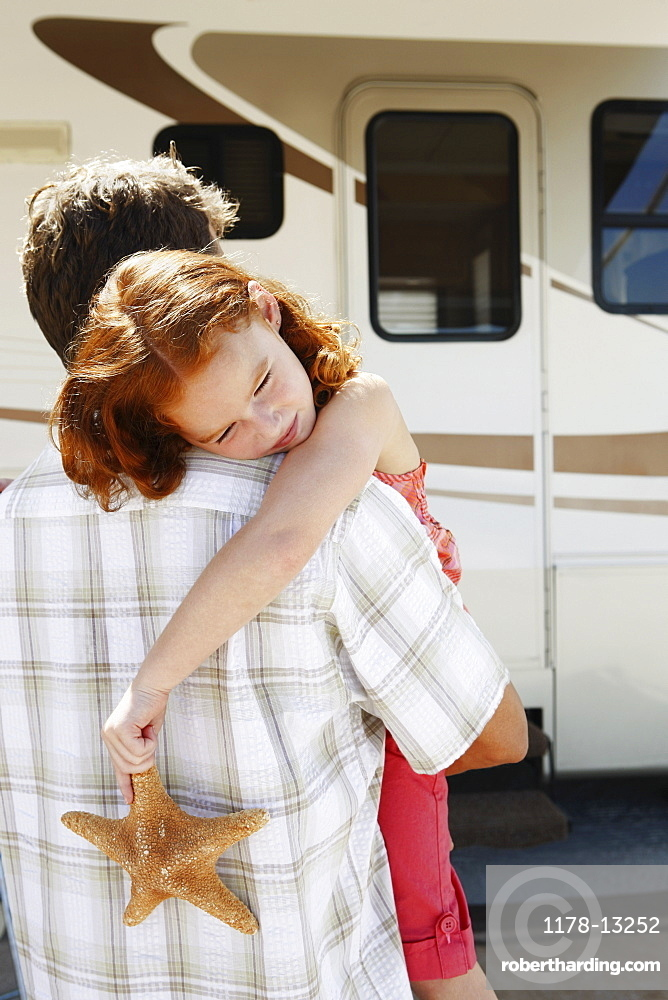 Father carrying sleepy daughter and starfish to motor home