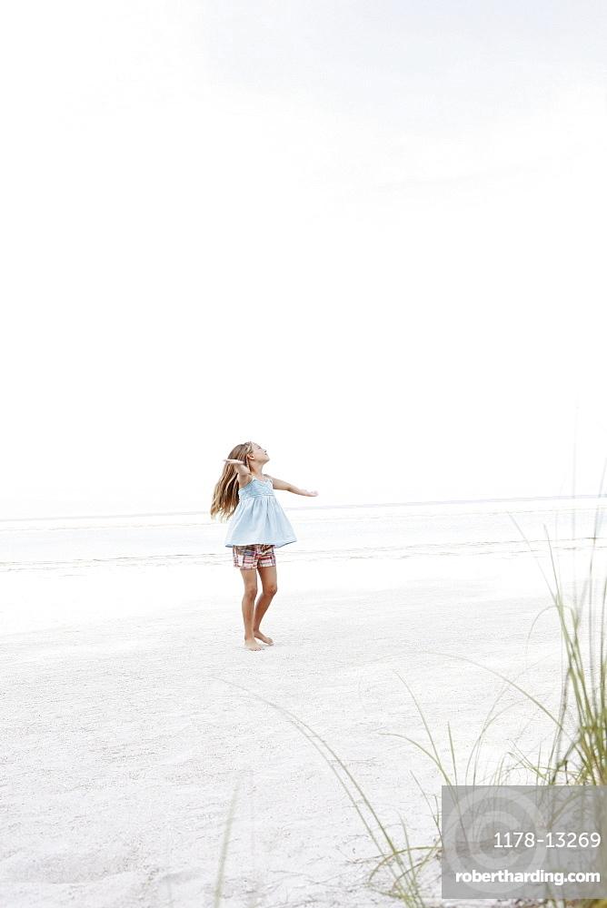 Girl twirling in beach