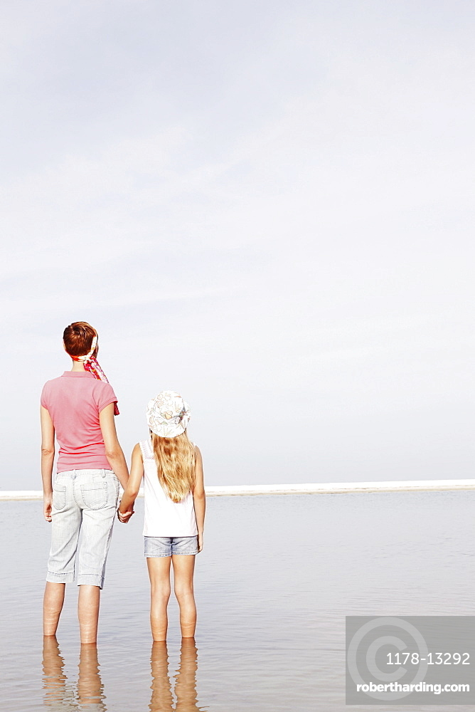 Mother and daughter holding hands on beach