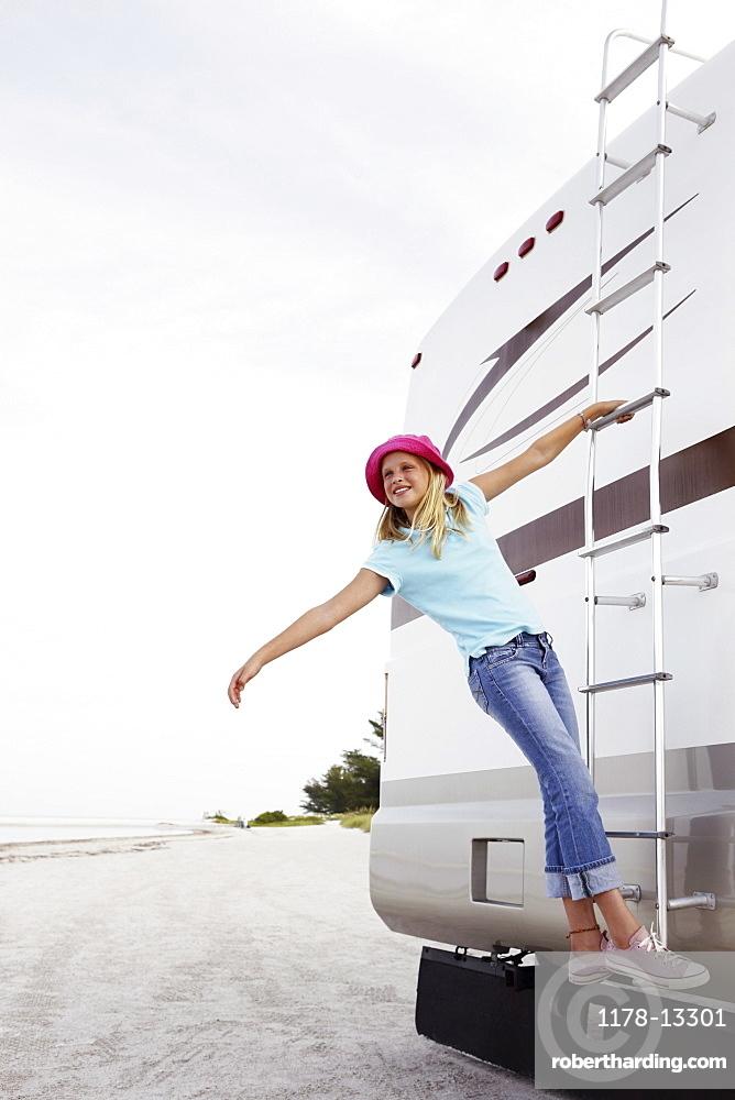 Girl climbing on motor home ladder