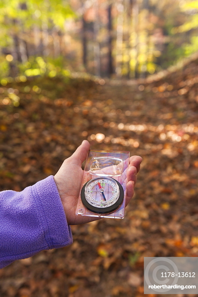 USA, New Jersey, Close-up of woman's hand holding compass in Autumn forest