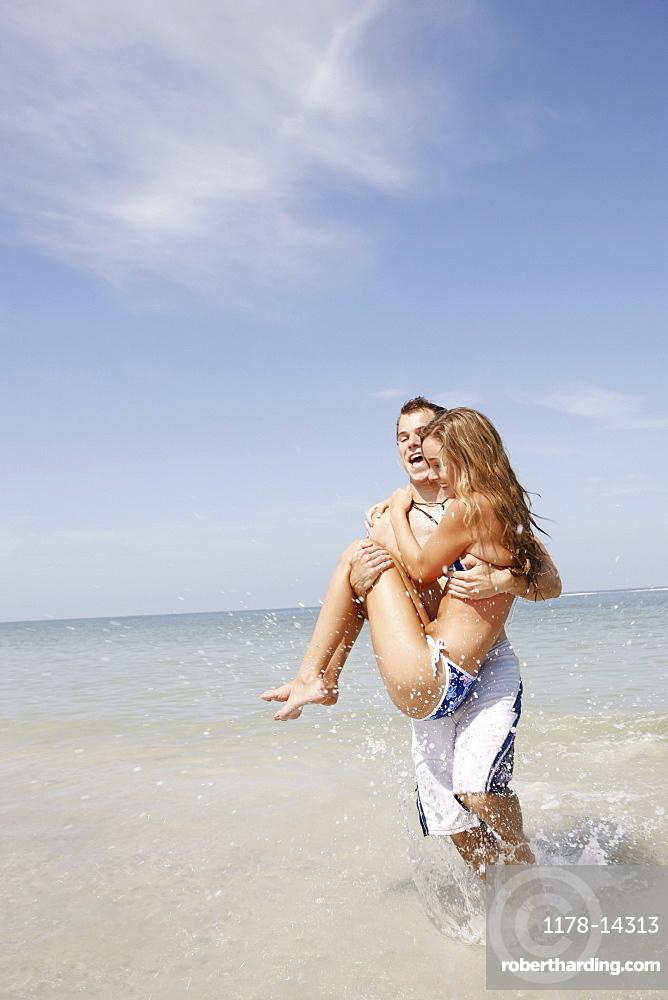 Man carrying girlfriend in ocean surf