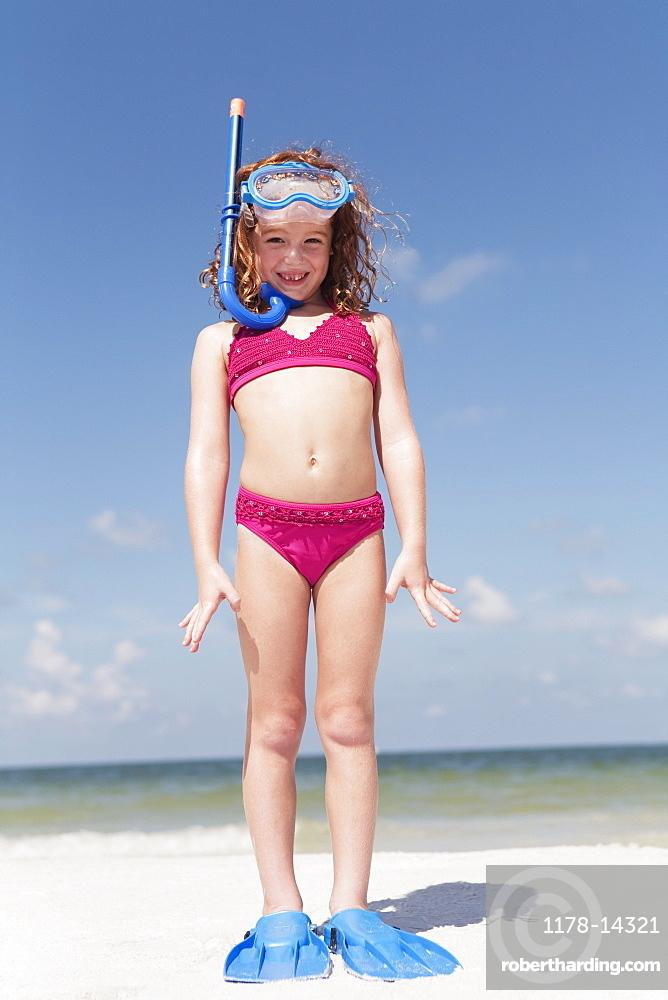 Girl on beach wearing snorkeling equipment