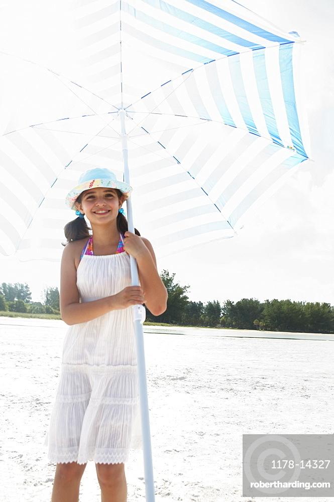 Girl holding umbrella on beach