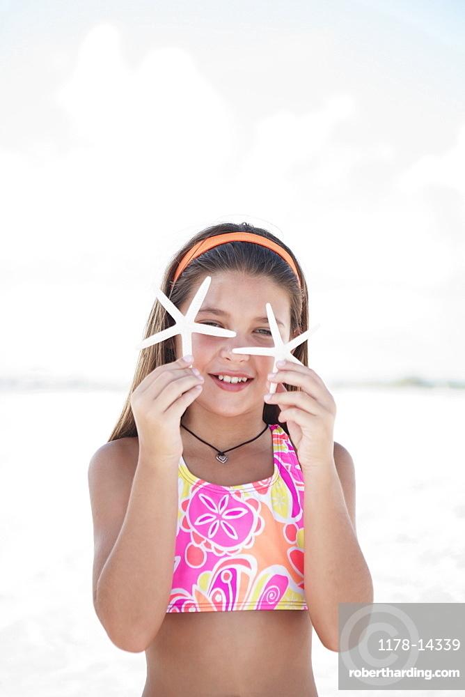 Girl on beach holding delicate starfish