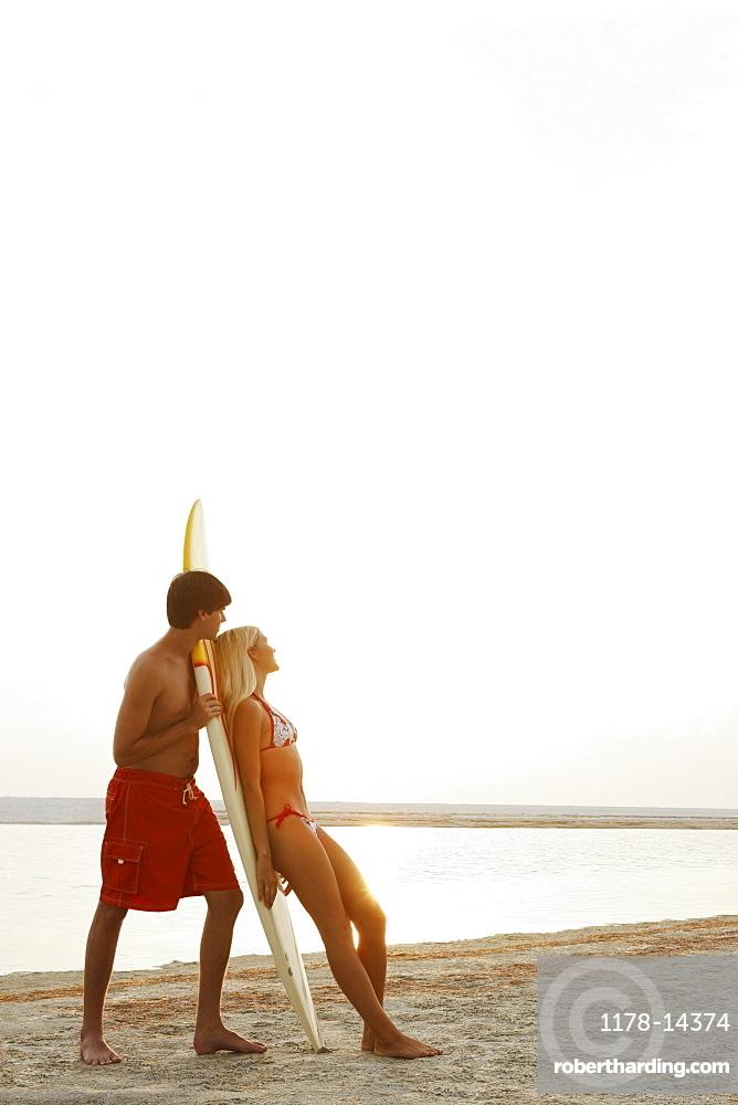 Young couple enjoying sunset on beach