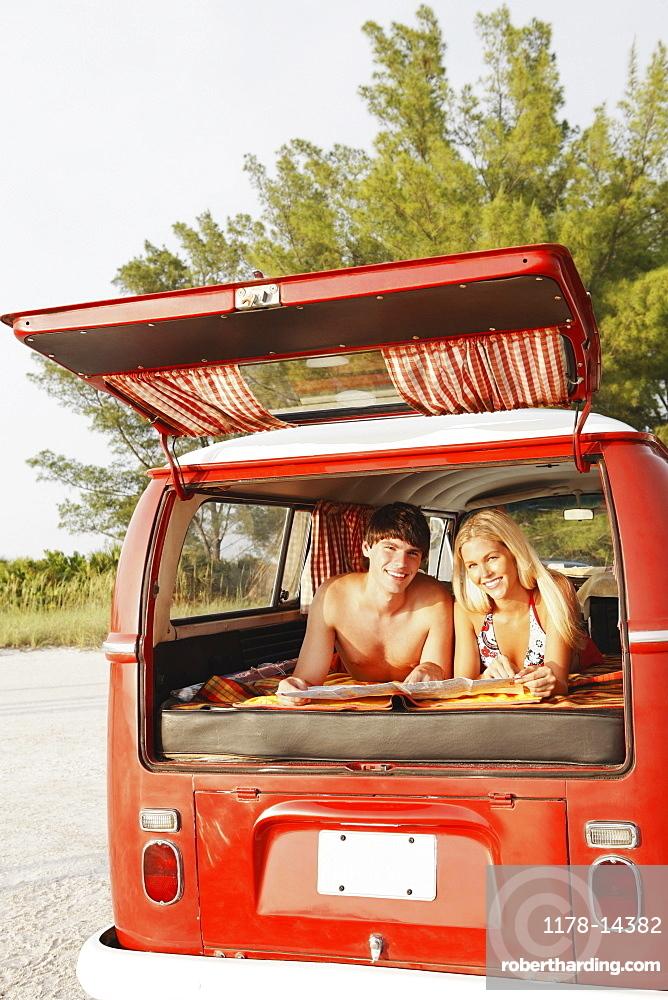 Teenage couple relaxing in van on beach
