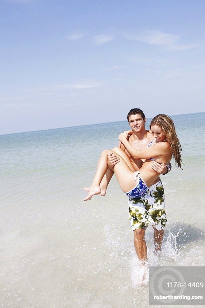 Teenage boy carrying girlfriend in ocean