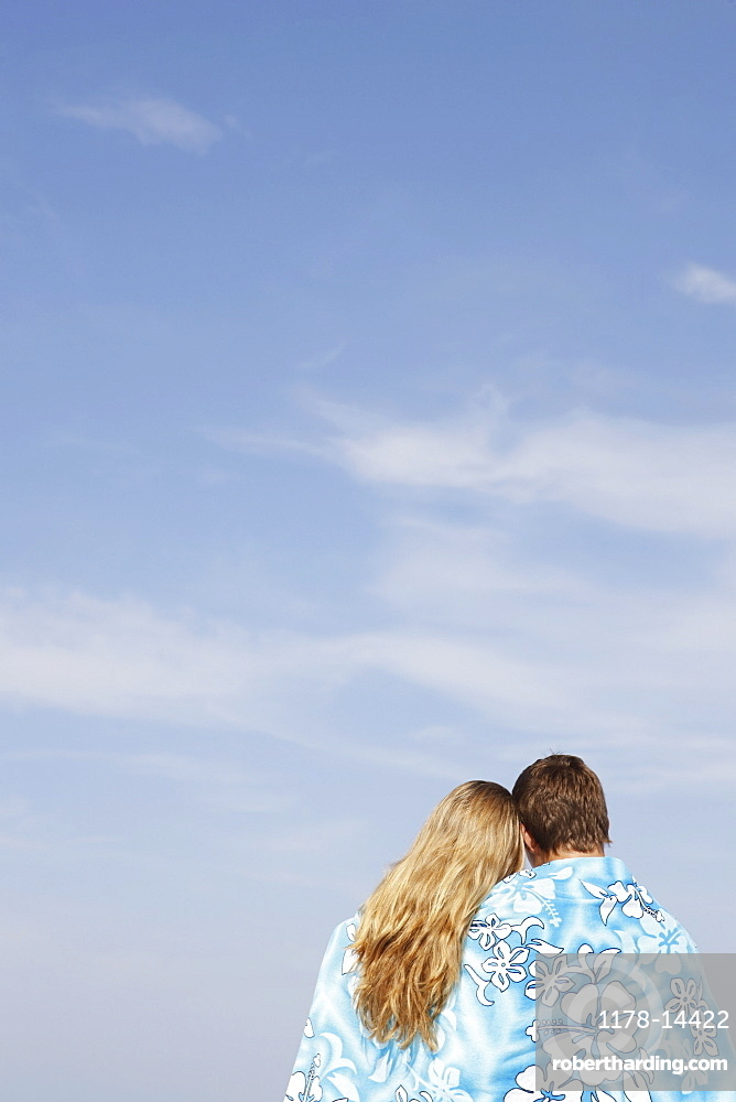Teenage couple hugging under towel on beach