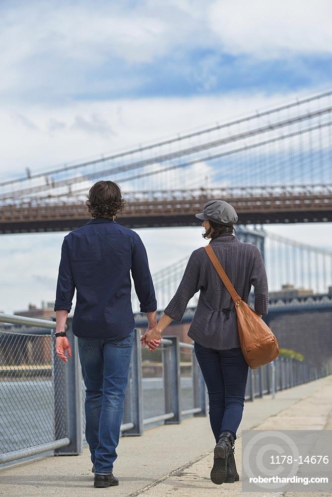 Rear view of couple walking on promenade, Brooklyn Bridge in background, Brooklyn, New York