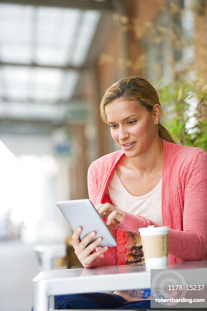 Woman using tablet in cafe