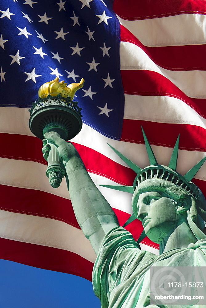 Statue of liberty under US flag, USA, New York City