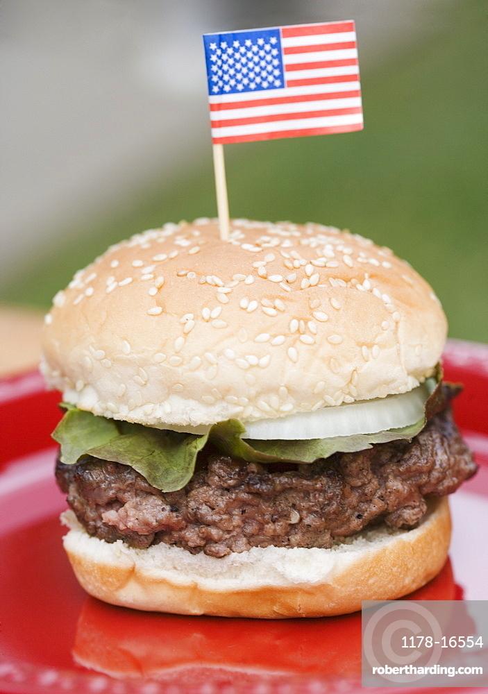 Still life of hamburger with small US flag